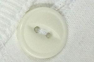 今では珍しい猫目ボタン。糸を守るための凹みがついています。